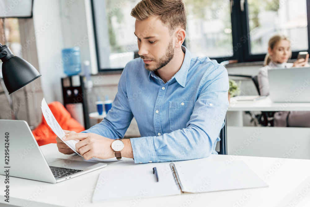 Fototapeta young businessman holding papers and working with laptop in office