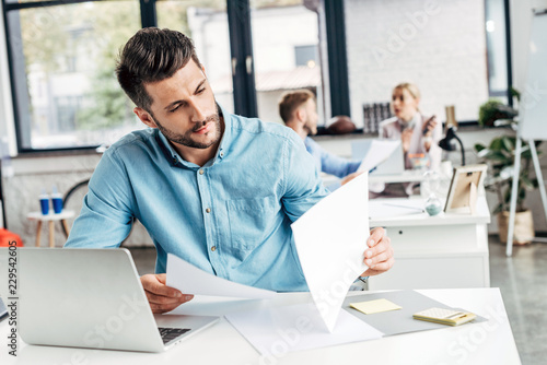 concentrated young businessman working with papers and laptop in office - fototapety na wymiar