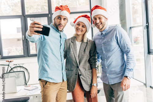 Fototapety, obrazy: happy young start up team in santa hats taking selfie with smartphone in office