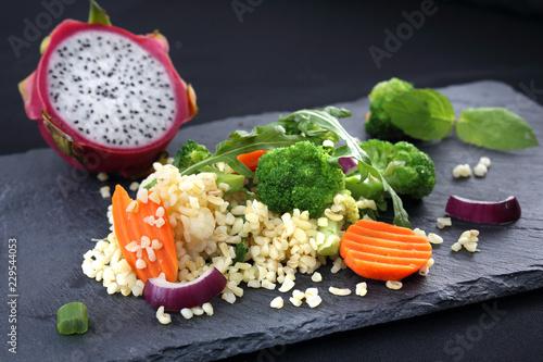Keuken foto achterwand Assortiment Danie obiadowe, ryż z brokułami i marchewką. Ryż brązowy z warzywami podana czarnym talerzu.
