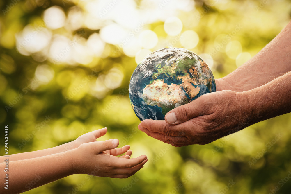 Fototapeta Close up of senior hands giving small planet earth to a child over defocused green background with copy space