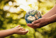 canvas print picture - Close up of senior hands giving small planet earth to a child over defocused green background with copy space