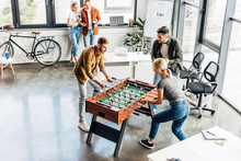 High Angle View Of Young Casual Business People Playing Table Football At Office And Having Fun Together