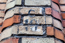 House Number Ten C 10C In Damaged Black Paint On Red House Brick Wall In Belgium