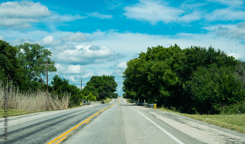 Foto op Plexiglas Texas Rural road in Texas, USA. Agricultural landscape and blue sky