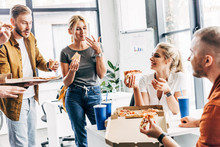 Group Of Successful Entrepreneurs Having Pizza For Lunch Together While Working On Startup At Office