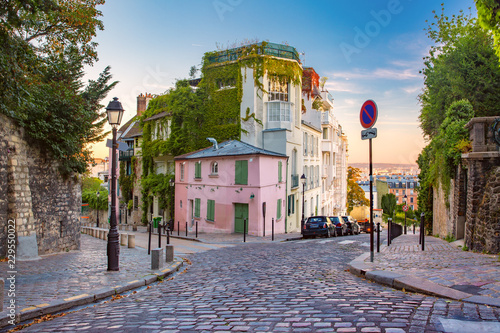 Photo Stands Historical buildings Cozy old street with pink house at the sunny sunrise, quarter Montmartre in Paris, France