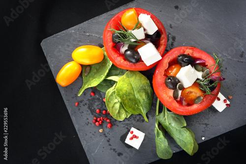 Pomidory nadziewane. Pomidory faszerowane oliwkami, serem feta, szpinakiem podane na czarnym talerzu.