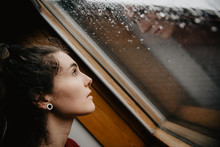 Young Woman Looking At Wet Win...