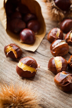 Roasted On The Open Fire Sweet Chestnut Nuts On Wooden Rustic Natural Background. Perfect Traditional Meal For Christmas.