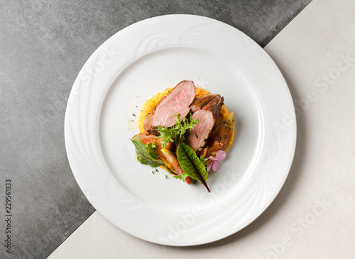 Duck fillet with figs and carrot puree on a white plate