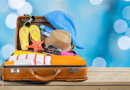 Fotografia  Retro suitcase with travel objects on wooden