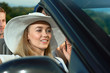 Blonde in white brim broad hat going for a drive in cabriolet.