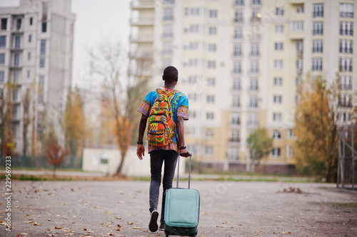 African man in africa traditional shirt on autumn park with backpack and suitcase Canvas Print