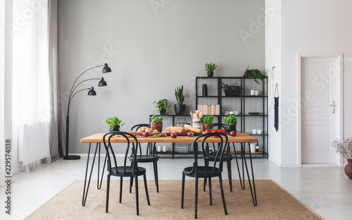 Black Chairs At Wooden Table With Food In Grey Dining Room Interior Plants And Lamp