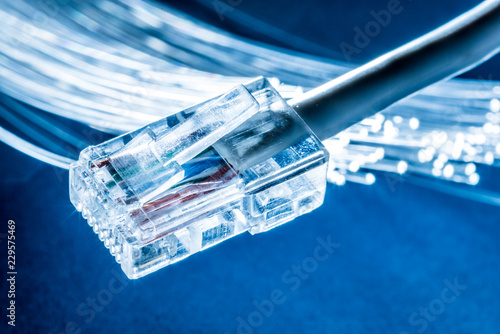 Network cable and optical fibers with lights in the ends at the background.
