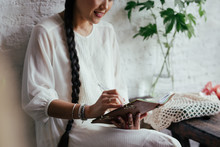 Elegant Cropped Asian Woman With Long Bride Writing In Her Notebook.