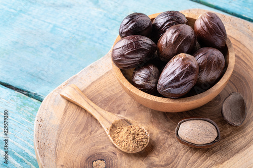 Fototapeta Whole inshell nutmeg nuts in a bowl and a spoon with nut powder on blue rustic wooden table. obraz