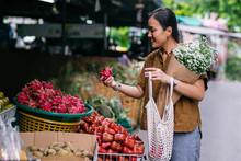 Beautiful Smiling Thai Woman Picking A Dragon Fruit On Outdoor Food Market.