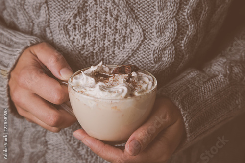Hands holding cup of chai latte, toned Fototapeta
