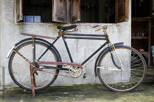 Vintage bicycle leaning on raw cement wall.