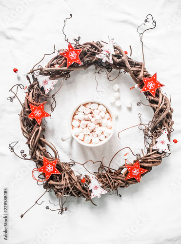 Homemade Christmas vine wreath with red wooden stars and hot chocolate with marshmallows on white background, top view. Copy space, flat lay