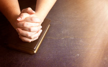Woman Praying With Her Hands Clasped On A Bible