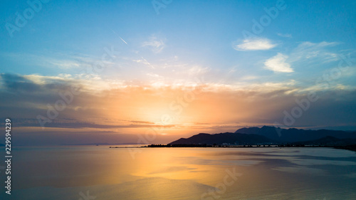 Inspirational beautiful sunset landscape at sea and mountains