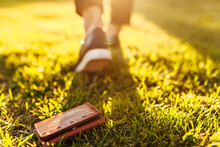 The Girl Lost A Leather Wallet With Money On The Street. Close-up Of A Purse Lying On The Grass And Legs Of A Departing Girl