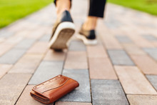 The Girl Lost A Leather Wallet With Money On The Street. Close-up Of A Wallet Lying On The Sidewalk And Legs Of A Departing Girl