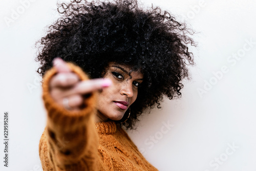 Portrait of attractive afro woman making fuck you sign Wallpaper Mural