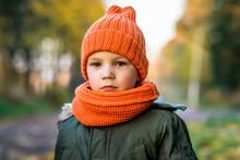 Boy In Orange Hat And Scarf In Park In Autumn
