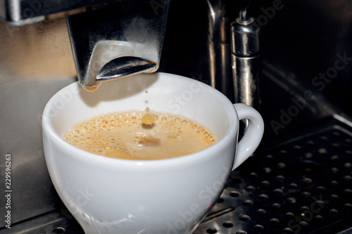 Making coffee in a coffee machine with white cup