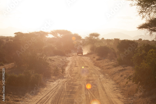 Safari vehicle driving into the sunset in Africa