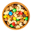 canvas print picture - Trail mix in wooden bowl. Snack mix. Almonds, cashews, peanuts, hazelnuts, raisins and colorful chocolate candies. Food to be taken along hikes. Macro food photo closeup from above on white background