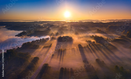 Aerial view of epic light rays over the fields at Autumn