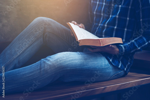 close up of man holding and read bible while sitting on wooden chair, Christian Canvas-taulu