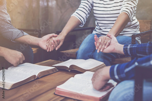 Fotografija christian small group holding hands and praying together around wooden table wit