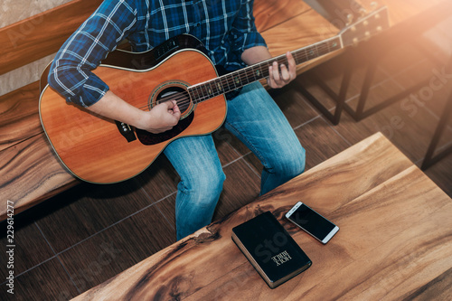 Top view of a man playing guitar with bible and smart phone on wooden table, Christian devotional worship concept - 229614277