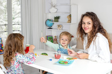 Little Children With A Nanny Or With A Young Mother Or With A Teacher To Prepare For Christmas.  They Sit At The Table In The Room And Paint Christmas Gingerbread Or Toys.