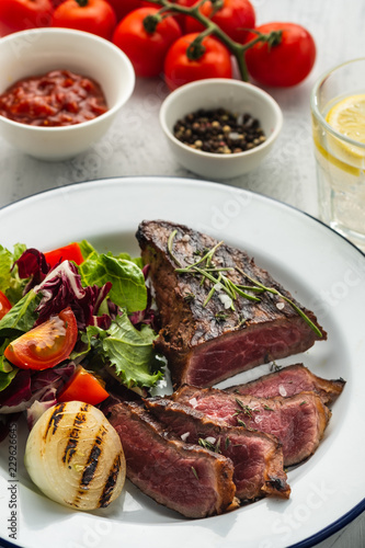 Delicious beef steak with salad. Sliced grilled beef barbecue with fried onion