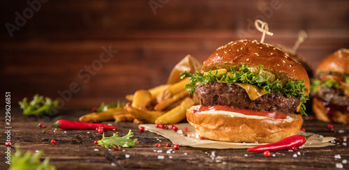 Delicious hamburger with fries, served on wood