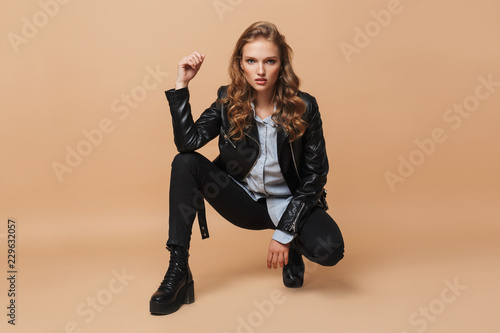 Obraz Beautiful serious girl with wavy hair in black leather jacket and shirt thoughtfully looking in camera over beige background isolated - fototapety do salonu