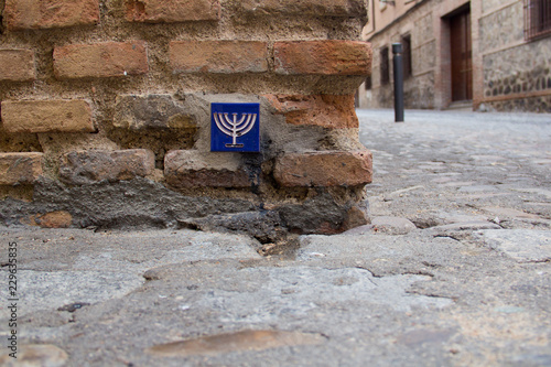 A blue pottery tile with a yellow menorah on it in a brick wall in the Jewish quarter of Toledo, Castile-La Mancha, Spain, a UNESCO World Heritage Site