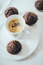 Mini Chocolate Muffins On White Plate With A Cup Of Coffee In The Middle. High Angle Shot, White Background.
