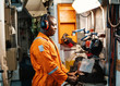 African marine engineer officer in engine control room ECR. He works in workshop with equipment