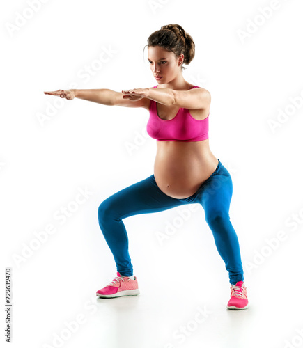 Sporty pregnant girl squatting, doing sit-ups isolated on white background Canvas Print
