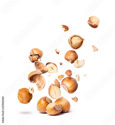 obraz lub plakat Сracked hazelnuts fall down isolated on white background