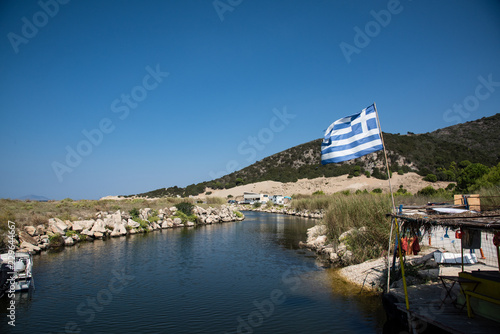 Fotografie, Obraz  Greek flag flying over the river channel