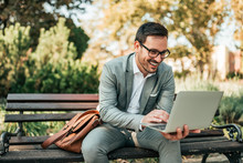 Handsome Businessman Using Laptop In The Park.